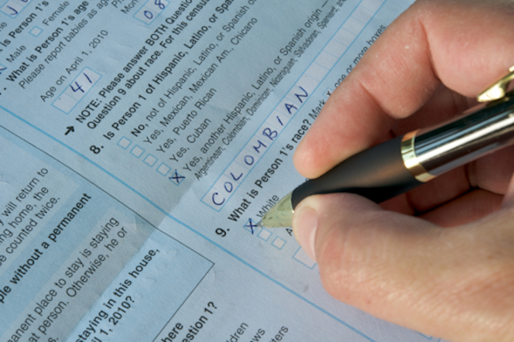 A person's hand documents their Hispanic ethnicity on a census form.